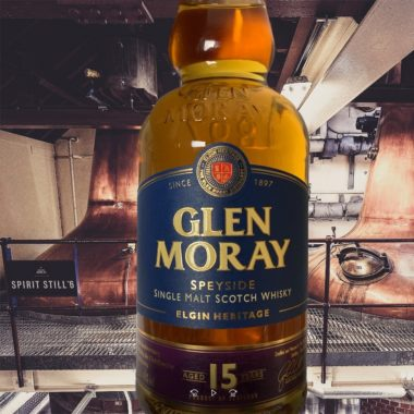 Glen Moray 15 years single malt bottle in front of stills in production