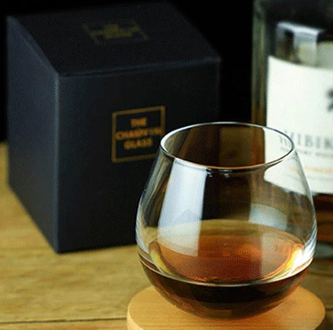 Round Slow Roll Whisky Glass stands upright on flat table